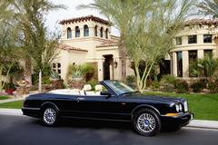 Luxurious convertible car parked in front of a mansion house Stock Photos