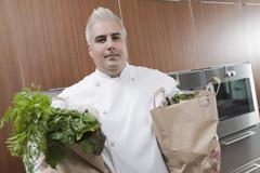 Chef With Bags Of Groceries In Commercial Kitchen Stock Photos