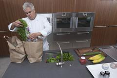 Stock Photo of Chef Unpacking Groceries From Paper Bags In Kitchen