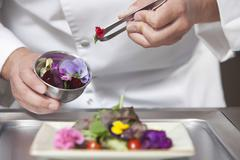 Chef Arranging Edible Flowers On Salad Stock Photos