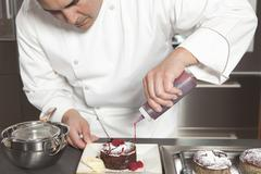 Chef Puts Finishing Touches On Chocolate Cake At Kitchen Counter Stock Photos
