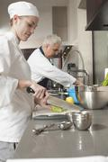 Chefs Working In Commercial Kitchen - stock photo