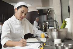 Female Chef Writing On Clipboard In Kitchen - stock photo