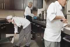 Chefs Working Together In Commercial Kitchen Stock Photos