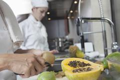 Chef Peeling Tropical Fruit In Kitchen Stock Photos