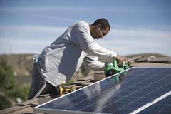 Man Working On Solar Panelling On Rooftop Stock Photos