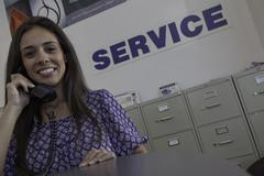 Woman attending a call at automobile repair shop Stock Photos