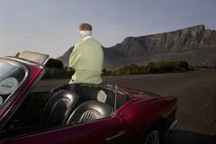 Man Admires View Leaning On Vintage Car - stock photo
