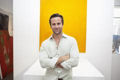 Stock Photo of Half-length portrait of smiling young man in front of yellow painting