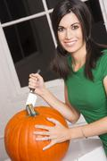 excited woman cutting carving halloween pumpkin jack-o-lantern - stock photo