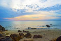 Stone at sea shore with sunrise background Stock Photos