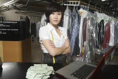 Confident Woman With Receipt Spike And Laptop On Counter In Laundry Stock Photos
