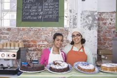 Mother And Daughter In Aprons Standing At Cake Shop Counter - stock photo