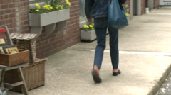 Woman walking quickly down sidewalk Stock Footage