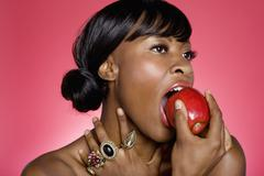 Close up of woman biting an apple over colored background - stock photo
