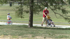 Father pushing stroller while son rides bicycle (2 of 2) Stock Footage