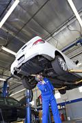Technician working on car at automobile repair shop - stock photo