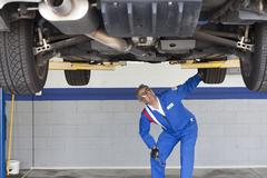 Mechanic checking the car at automobile repair shop Stock Photos