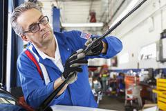 Mechanic working on windshield wipers of car Stock Photos