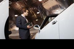 Salesman standing in automobile showroom Stock Photos