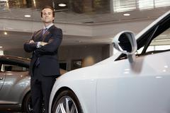 Confident car salesperson standing with arms crossed Stock Photos