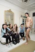 Male stripper posing in front of women Stock Photos