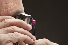 Cropped image of jeweler examining jewel over black background Stock Photos