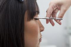 Close-up view of hairstylist cutting hair Stock Photos