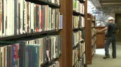 Man searching bookshelf in library (1 of 4) Stock Footage