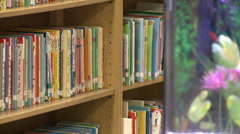 Fish tank near children's books on library shelves (2 of 2) Stock Footage