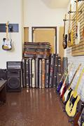 Electric guitars with guitar cases and amplifier in store Stock Photos