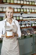 Portrait of a happy senior female employee holding spice jar in store Stock Photos