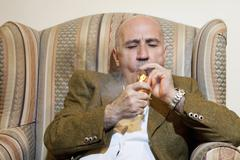Mature man igniting cigar while sitting on armchair - stock photo