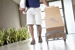 Low section of a man walking with packages on handtruck Stock Photos