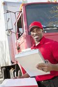 Stock Photo of Portrait of a happy African American man holding clipboard with delivery truck