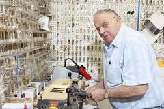 Senior locksmith looking away while making key in store - stock photo
