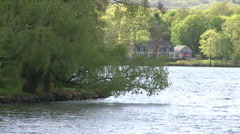 Cottage in distance across water Stock Footage