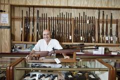 Portrait of a happy weapon shop owner - stock photo