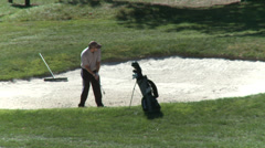 Golfer chipping out of sand trap - stock footage