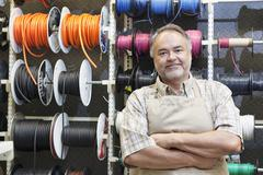 Portrait of a happy mature salesperson standing in front of electrical wire - stock photo