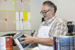Happy mature sales clerk reading instructions paint can in hardware store Stock Photos