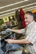 Mature man looking at price tag of machinery in hardware store - stock photo