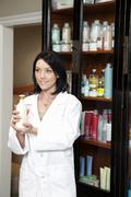 Stock Photo of Happy beauty salon employee holding cosmetic products while looking away