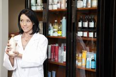 Stock Photo of Happy beauty salon employee looking away while holding cosmetic products