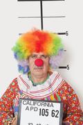 Portrait of senior clown posing for mug shot - stock photo
