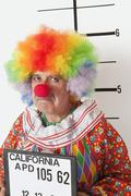 Portrait of angry senior clown during mug shot - stock photo