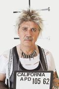 Mug shot of serious senior male punk - stock photo