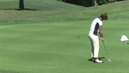 Stock Video Footage of Female golfer putts ball and is excited (1 of 2)