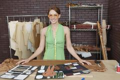 Portrait of pretty female fashion designer standing at table with layouts Stock Photos