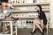 Stock Photo of Happy mid adult woman trying high heels in footwear store